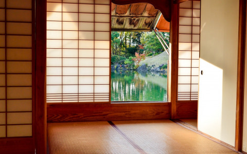 Interior of Japanese home with paper walls and door opening onto pond and garden