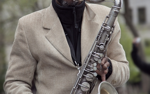 Man in coat hat and sunglasses playing saxophone outdoors