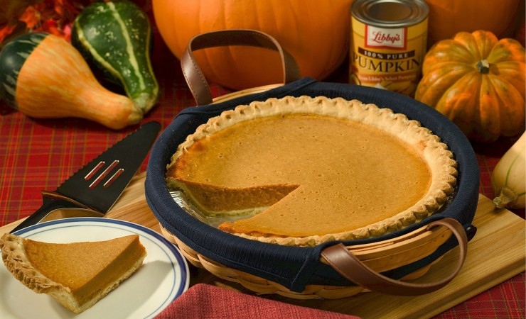 Pumpkin pie in basket alongside decorative gourds on table