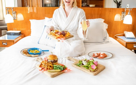 a woman eating room service in a white robe