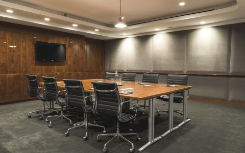 black chairs around a wood conference table