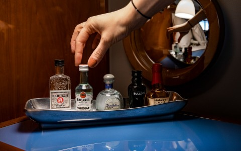 a woman choosing a small bottle of liquor from the mini fridge