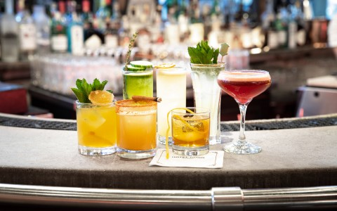 brightly colored cocktails lined up at the bar