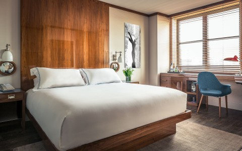 a king size bed in a guest room with wood on the walls