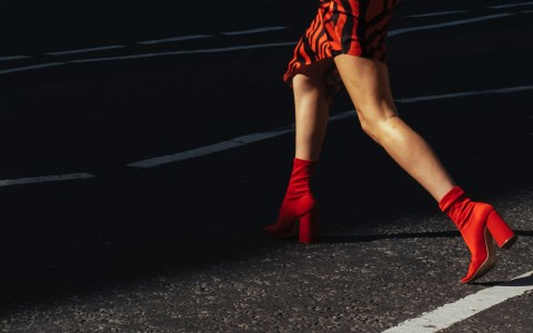 a woman in red high heels walking at night