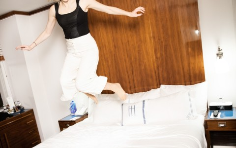 a women jumping on the bed