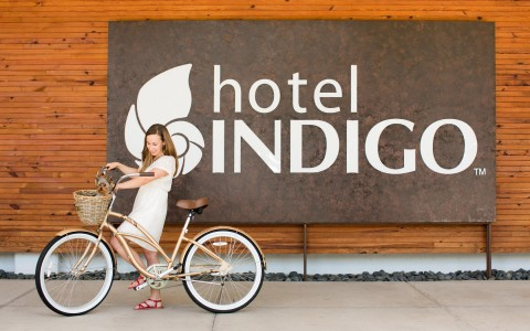 woman on bike in front of Hotel Indigo sign