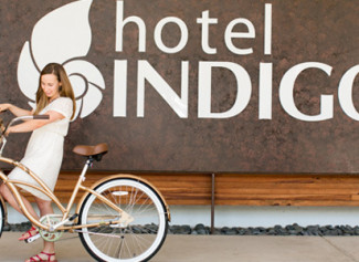 hotel indigo athens woman on bike in front of sign