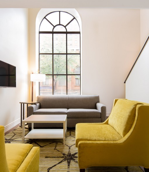 Living space in room with yellow couches