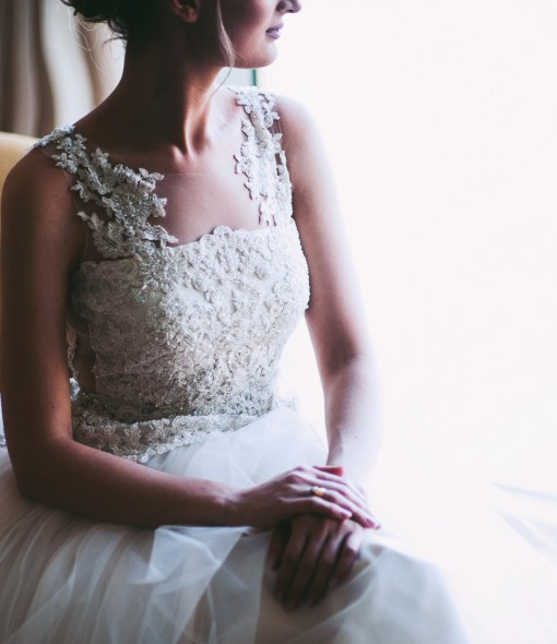 Bride in dress next to window