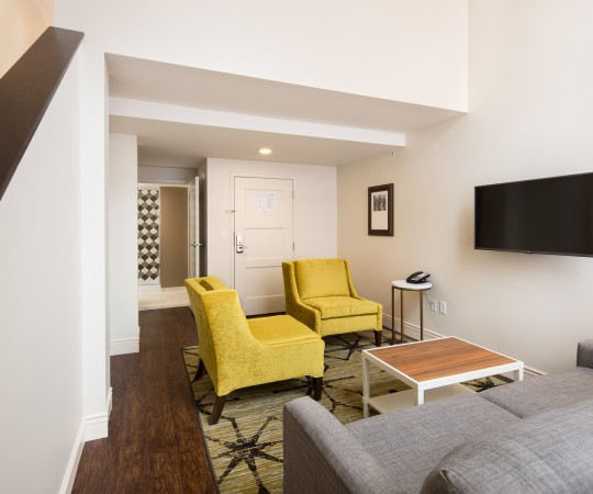 Baltimore Bi Level suit seating area with mustard yellow accent furniture and sofa across from mounted tv and stairs