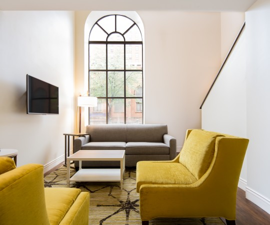 Baltimore Bi Level suit seating area with mustard yellow accent furniture across from mounted tv and stairs