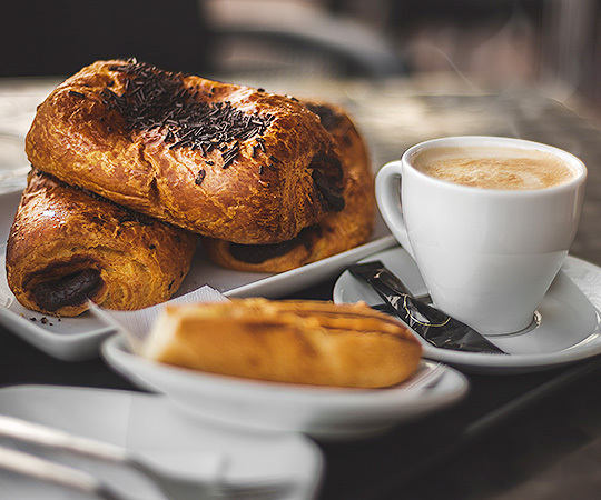 Trio of chocolate breakfast croissants on a plate next to a cup of coffee and a piece of toast.