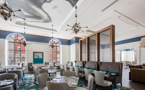 Poets Restaurant with its warm, playful and contemporary vibe. Features a long bar with white high top leather bound chairs. Long tables to dine and drink, lounge seating area, booth and chair combination seating. Large glass window pane windows go from f