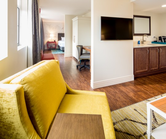 Indigo Baltimore suite has an industrial chic look. Wood and earth tones. living room containing kitchenette, seating area, mounted tv leading into bedroom