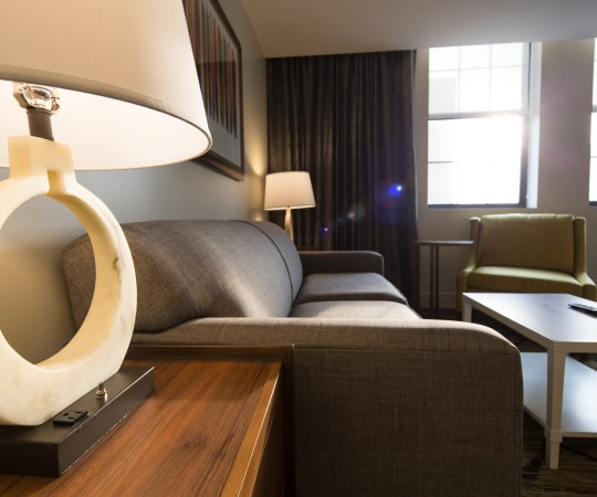 King Suite seating has long leather couch with coffee table and side table with lamp