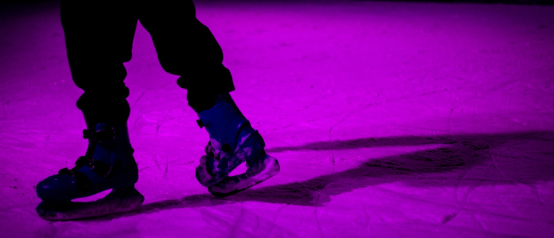 Person ice skating with focus on two legs and purple light on the ice