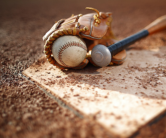 Baseball glove with ball and bat resting on a dirty home plate of a baseball field