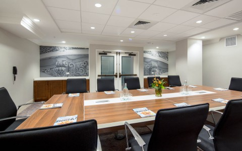 meeting room with a large wood table and black leather swivel chairs set up for a meeting
