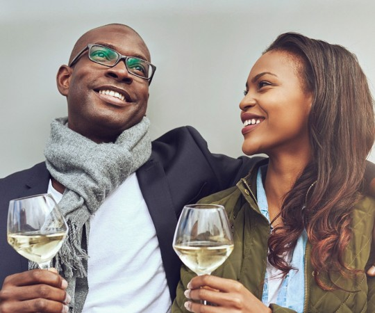 man and women in winter attire. Mans arm around women, both with a glass of white wine