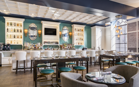 Poets Restaurant with its warm, playful and contemporary vibe. Features a long bar with white high top leather bound chairs. Long tables to dine and drink, lounge seating area. Teal and white are the color palette of this chic bar.