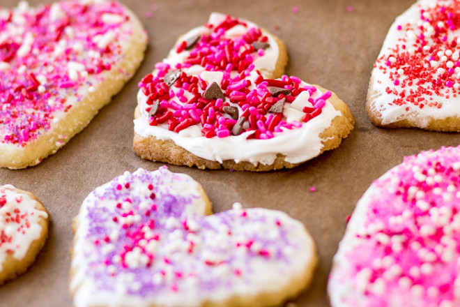 heart shaped cookies with white frosting and pink and purple sprinkles