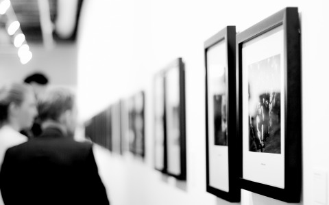 Black and white image of framed art and onlookers
