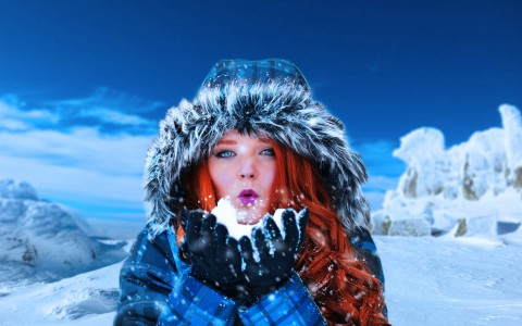 Ethereal woman in parka amid icy landscape blows snow at the viewer