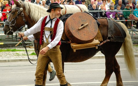 German man in traditional Bavarian attire with Oktoberfest horse
