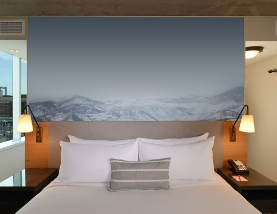 bed with mountain art above headboard