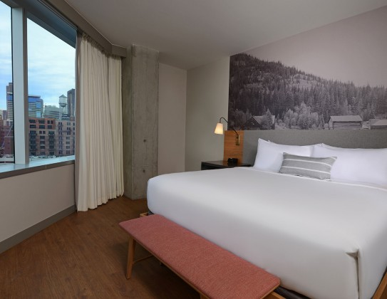 room with art on wall above bed and view of downtown Denver