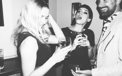 two women and a man holding drinks and laughing