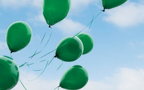 green balloons floating in the sky