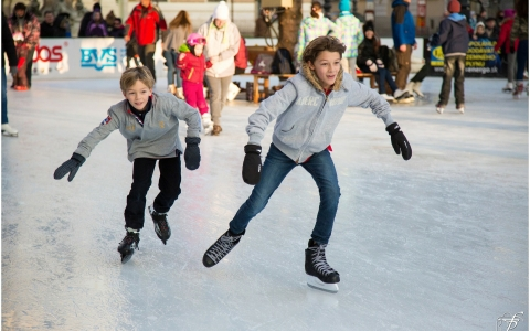 Two boys ice skating in gray sweatshirts jeans black gloves and black skates