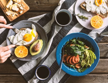 Brunch spread with avocado toast, coffee and a salad on top of a wooden table