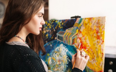 artist painting on colorful canvas