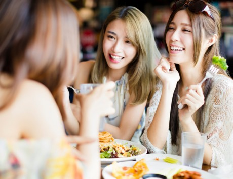 women talking and laughing over lunch