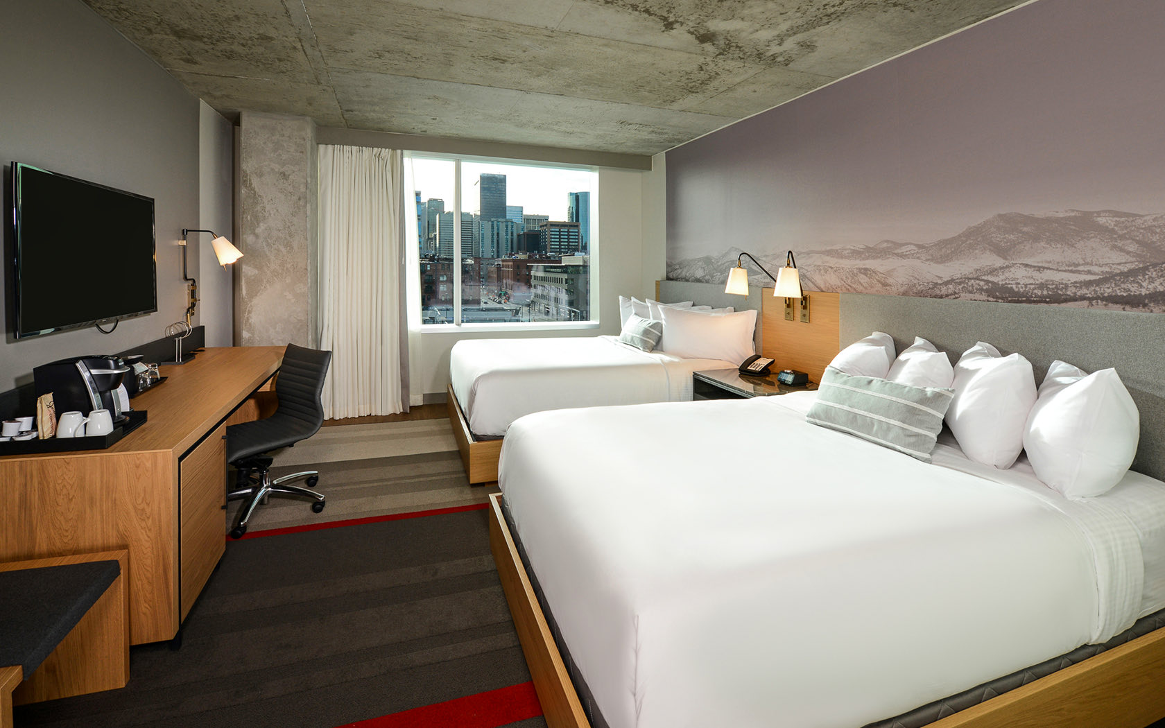 large hotel room with view of the city nd two queen beds