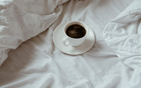 a cup of coffee on a bed