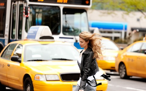 a woman walking in front of a taxi cab