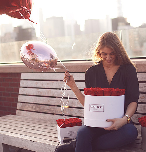woman holding red roses and two balloons