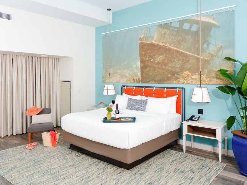 a king bed with a teal wall and painting of a ship