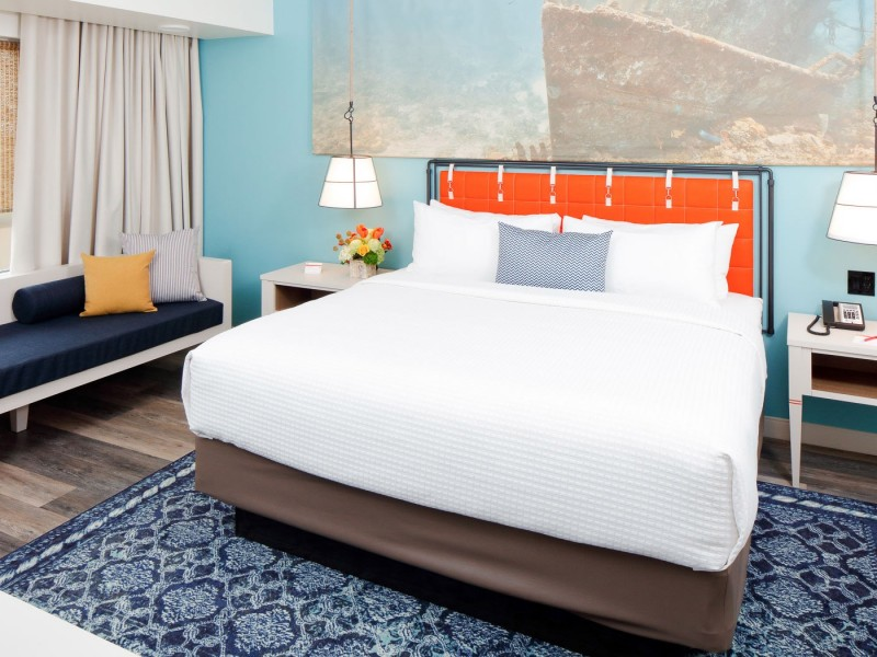 a king bed with orange headboard and white linens