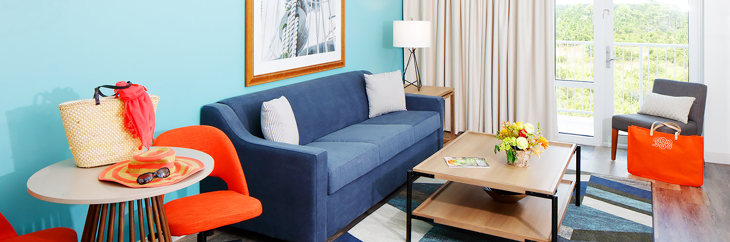 a blue couch in the sitting area of a guestroom