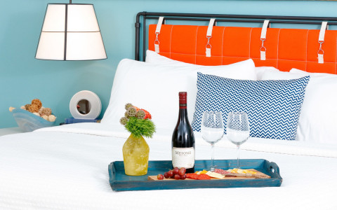 wine and cheese serving tray on white bed linen