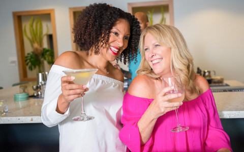 two ladies enjoying drinks and laughing together