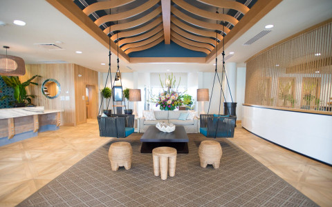 lobby area with swing bench seating and high ceiling with wooden design