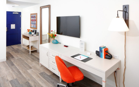 guest room with sitting desk and orange swivel chair