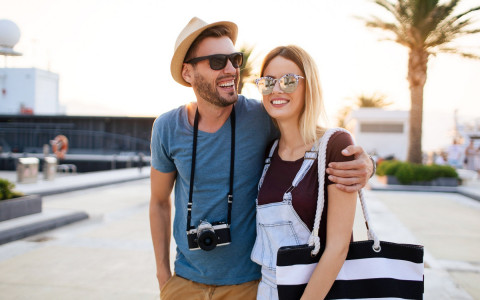 tourist couple walking together in sunglasses with camera