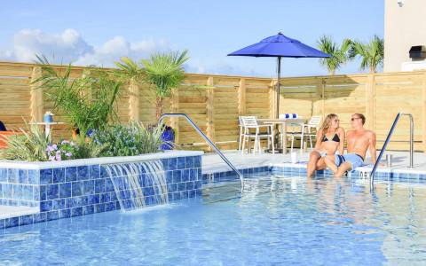 couple sitting at pool area with water feature and wooden fence surrounding